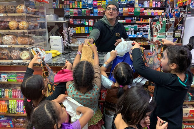 A local convenient store worker, hands out candy to trick or treaters on Halloween 2018 in Brooklyn Borough of New York. U.S. sales of Halloween candy were up 13% over last year in the month ending Sept. 6, according to data from market research firm IRI and the National Confectioners Association.