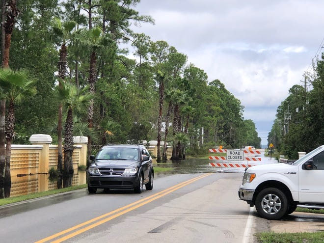 A vehicle moves past a barricaded section of County Road 393 last week in Walton County in the aftermath of Hurricane Sally. As roads or parts of roads across the county have remained closed in the wake of the hurricane, some motorists have begun moving the barricades out of affected roadways.