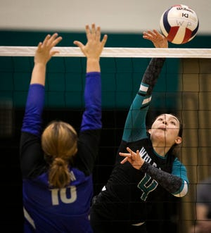 West Port's Paola Briceno-Lago spikes one over the net it the second set. The Wolf Pack defeated the Belleview Rattlers in four sets at West Port High Tuesday night.