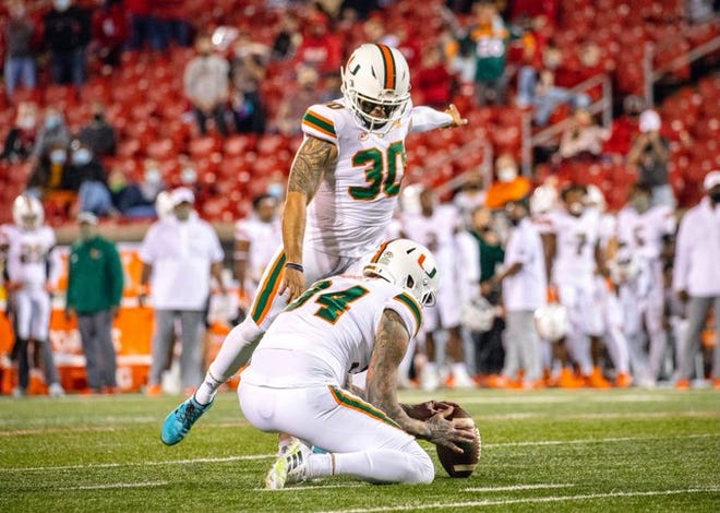 Miami's Jose Borregales kicks one of his four field goals last week at Louisville. Punter Lou Hedley is holding. [MIAMI ATHLETICS]