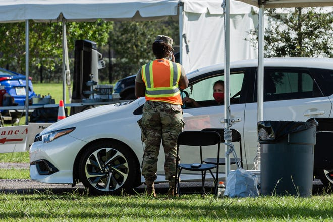 A woman gets checked in at the COVID-19 testing site at the FITTEAM Ballpark of the Palm Beach on Sept. 23.
