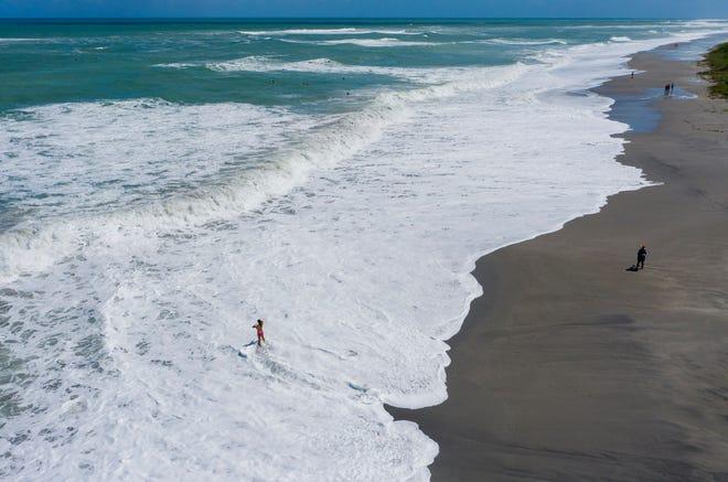 The ocean washes over the beach during high tide in Jupiter, Florida on September 23, 2020. (Greg Lovett / The Palm Beach Post)