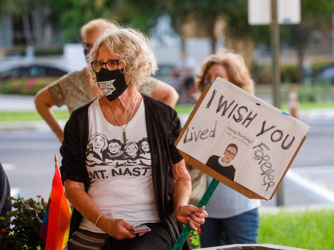 A woman holds up a sign during a vigil to remember U.S. Supreme Court Justice Ruth Bader Ginsburg outside the Federal Courthouse in downtown West Palm Beach Thursday evening, September 22, 2020. DAMON HIGGINS/The Palm Beach Post