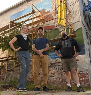 Artists Emily Ann Buckingham and Joshua Bentley are nearly done with the mural commissioned by Standing Rock Cultural Arts, led by Executive Director Jeff Ingram, right.