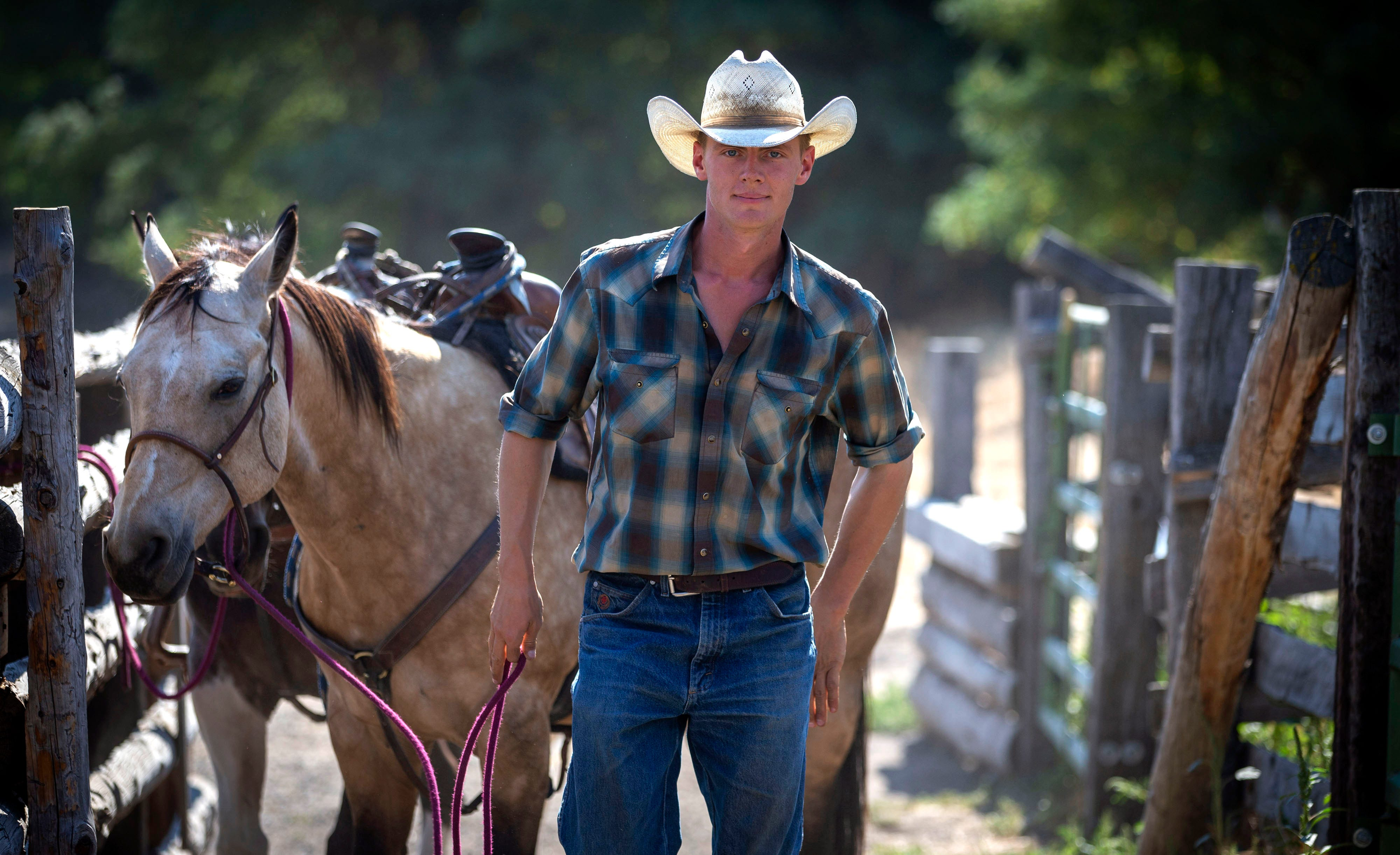 """Dima Anglin, a seventh-generation cattle rancher at Wilson Ranches in Wheeler County and a senior at Oregon State University, leads a horse to a barn on Sept. 4, 2020, in Fossil, Oregon. """"I saw this post on Facebook that was saying people in Eastern Oregon have been social distancing since long before it was cool."""""""