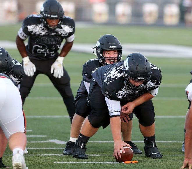 Perry center Dylan Smith prepares to snap the football to quarterback Hayden Vinas during a Sept. 11, 2020 game against Hoover. Perry running back Joshua Lemon (24) is in the background. (CantonRep.com / Scott Heckel)
