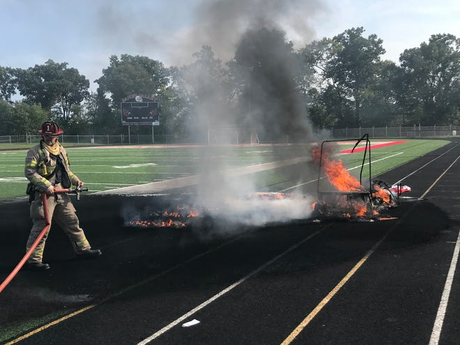 An East Sparta firefighter douses the fire that consumed a golf cart Wednesday inside Sandy Valley High School football stadium. The cause of the blaze is unknown.