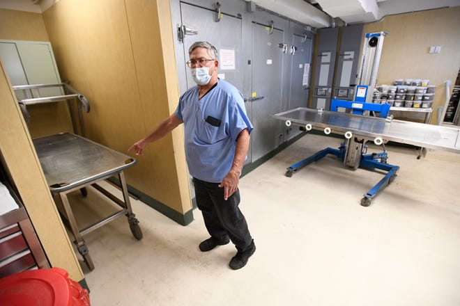 Stark County Coroner Anthony Bertin last week points to the cart used to hold a body while being autopsied in the county morgue at the Stark County Jail in Canton. He favors a move to the county-owned Lester Higgins Adult Center facility in Canton Township where his office would have more than double the space. (IndeOnline.com / Kevin Whitlock)