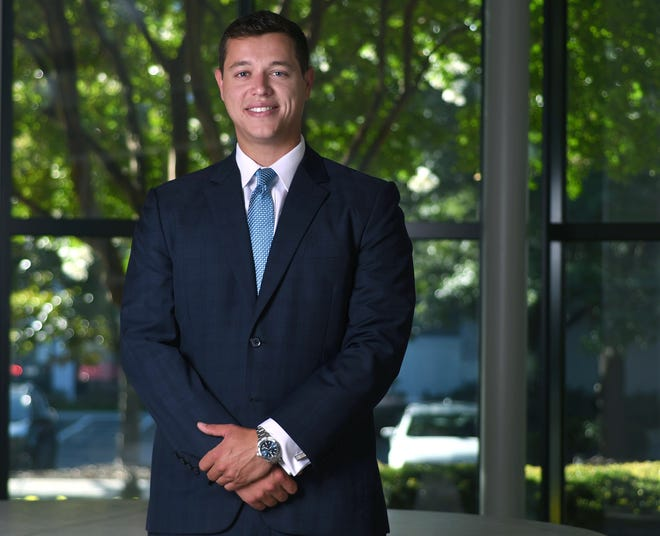 Riley Stephenson, Business Development Specialist with Decision Point Wealth Consulting, stands in the atrium at his office in Wilmington, N.C., Wednesday, July 22, 2020. Stephenson is one of the 40 Under 40 honorees for 2020. [REALTOR.COM]