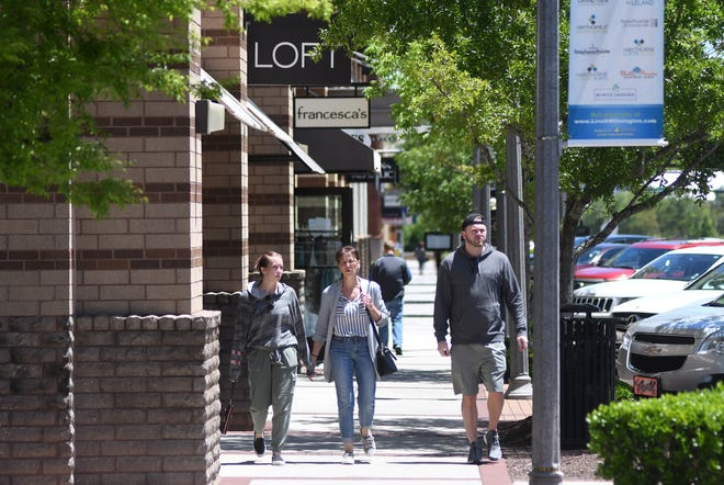People walk past the stores in Mayfaire in Wilmington, N.C., Saturday, May 9, 2020. [MATT BORN/STARNEWS]