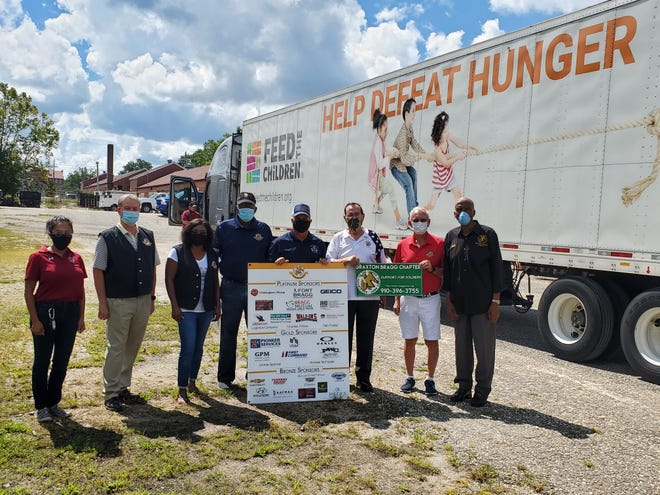 Members of the Association of the United States Army Braxton Bragg Chapter team up with Feed the Children to make a food donation to Fort Bragg's Family and Morale Welfare and Recreation program on Sept. 11.