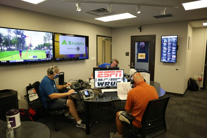 The Voice of the Gators Mick Hubert, right, and in-game producer Jeff Cardozo, center, work in the radio studio on the UF campus.