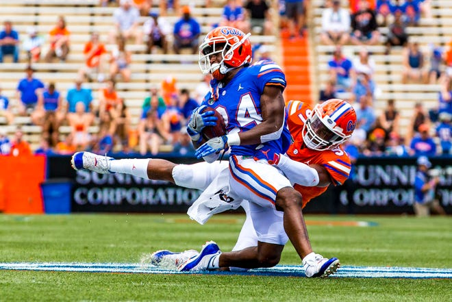 Florida running back Iverson Clement (24) is tackled by defensive back C.J. McWilliams (12) during the 2019 Orange and Blue Game.