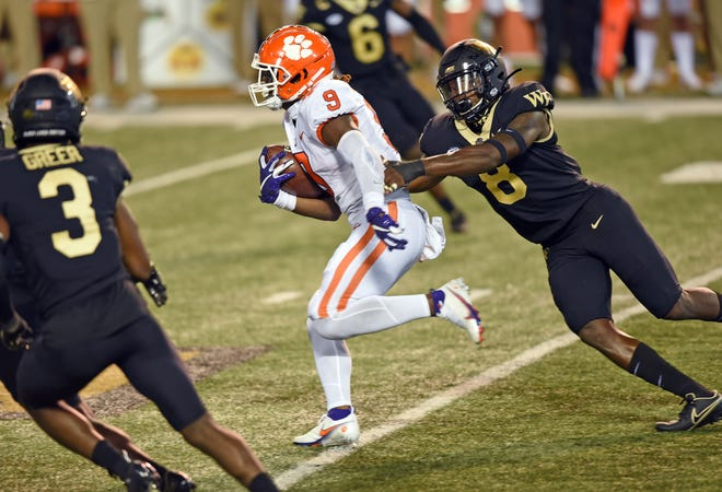 Wake Forest linebacker Ja'Cquez Williams, right, reaches out to try to corral Clemson running back Travis Etienne in the season opener.