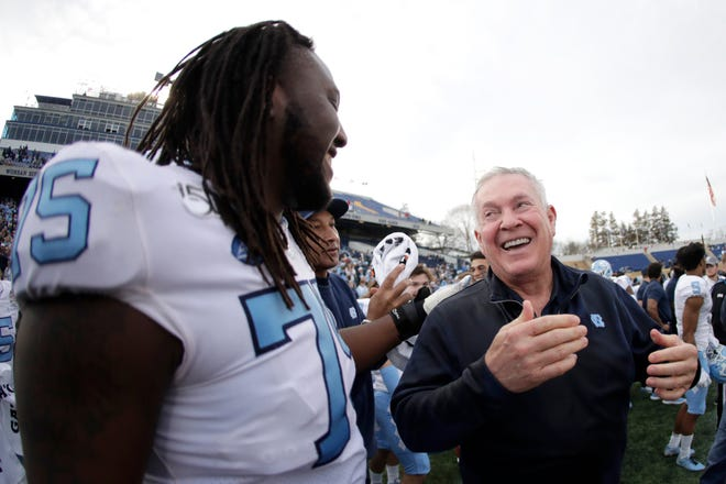 North Carolina offensive lineman Joshua Ezeudu, left, and coach Mack Brown celebrate the Tar Heels' blowout of Temple at the Military Bowl in December.