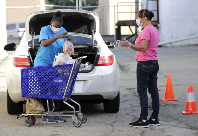 Elisa Laye, left, of Appleton picks up groceries from volunteer Jodi De Baker at Salvation Army-Fox Cities located at 130 E. North St. on Sept. 23 in Appleton.