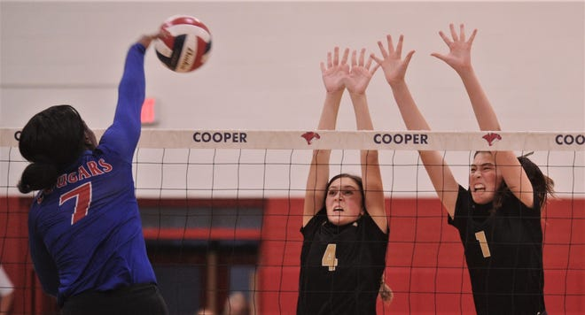 Cooper's Dazz Larkins, left, hits the ball as AHS' Jayden Hernandez (1) and Aven Horn defend. Cooper beat the Lady Eagles 25-9, 25-23, 25-23 in the nondistrict match Tuesday at Cougar Gym.