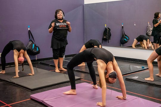 Studio owner and instructor Lisa DuBois leads dancers in backbends on Tuesday, Sept. 22, 2020 at Center Stage Dance Studio in Battle Creek, Mich.