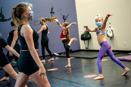 Dancers wear facemasks to an acrobatic and improvisation class on Tuesday, Sept. 22, 2020 at Center Stage Dance Studio in Battle Creek, Mich.