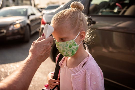 Primary Level One student Evie Frazer has her temperature taken on Tuesday, Sept. 22, 2020 before entering Center Stage Dance Studio in Battle Creek, Mich.