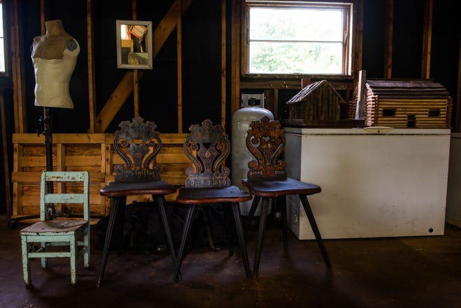 Antique chairs and log cabins stand on display in Matt Hranek's barn. He calls himself a curator. His wife says he's a hoarder.