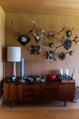Antlers adorn the wall above a midcentury console table.
