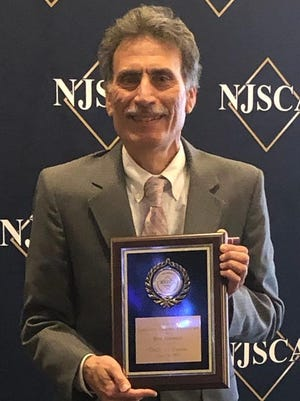 Bob Mannino, shown here accepting his New Jersey State Coaches Association Hall of Fame award induction plaque, has returned to coaching with the Schalick High School girls' soccer team.