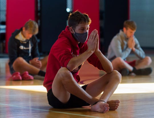 Cole Wirthwein performs namaste as the Southridge football players practice yoga at the Southridge High School field house in Huntingburg, Ind., Saturday morning, Sept. 19, 2020.