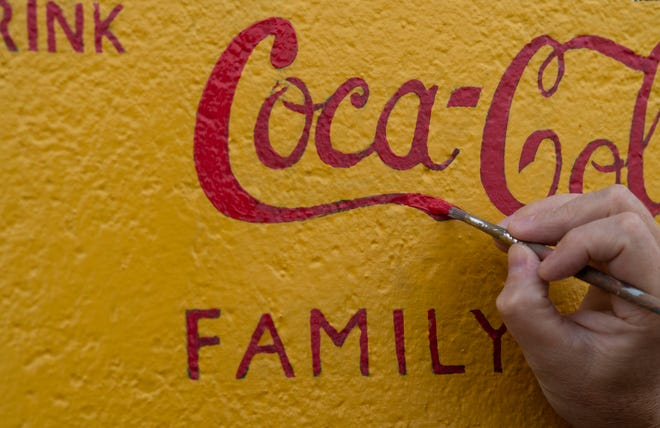 The Coca-Cola logo gets a brighter red hue from the tip of Sam Schaefer's paint brush Tuesday afternoon, Sept. 22, 2020.