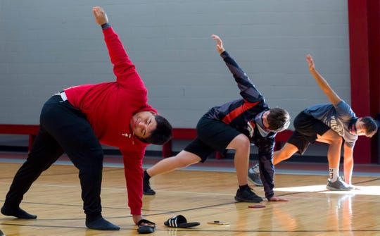Southridge football players Juan Mendoza, left, Scott Painter, center, and Matt Altmeyer, right, practice the yoga twisted present lunge at the Southridge High School field house in Huntingburg, Ind., Saturday morning, Sept. 19, 2020.