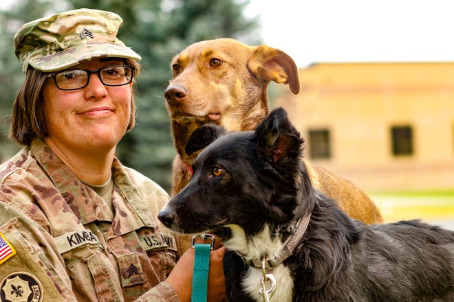 Sgt. Corina Kimball, an intelligence noncommissioned officer from Great Falls, Montana, with the 652nd Regional Support Group, sits with her dogs Cinnamon, left, and Pepper, right, September 14 at Fort William Henry Harrison, Helena, Montana. The pair became two of the first rescue dogs from Poland when they reunited with Kimball August 2 in Seattle, Washington.