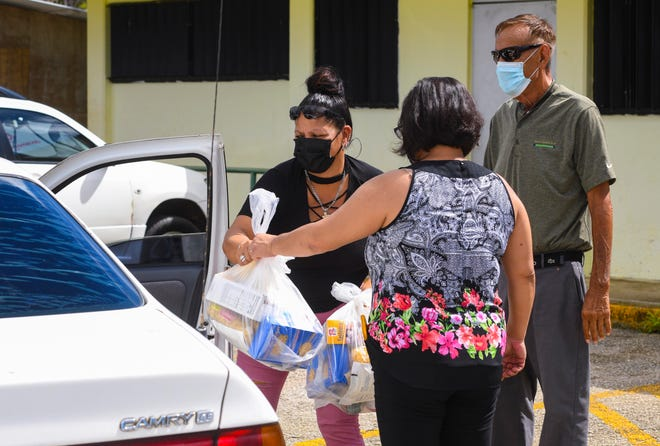 A driver receives non-perishable food packages from Beverly Campo and Mayor Vicente Taitague, right, during a drive-through food commodity distribution conducted at the Talofofo Mayor's Office in this Sept. 23 file photo. Food distribution continues in Umatac, Barrigada and Mongmong-Toto-Maite beginning Oct. 6.