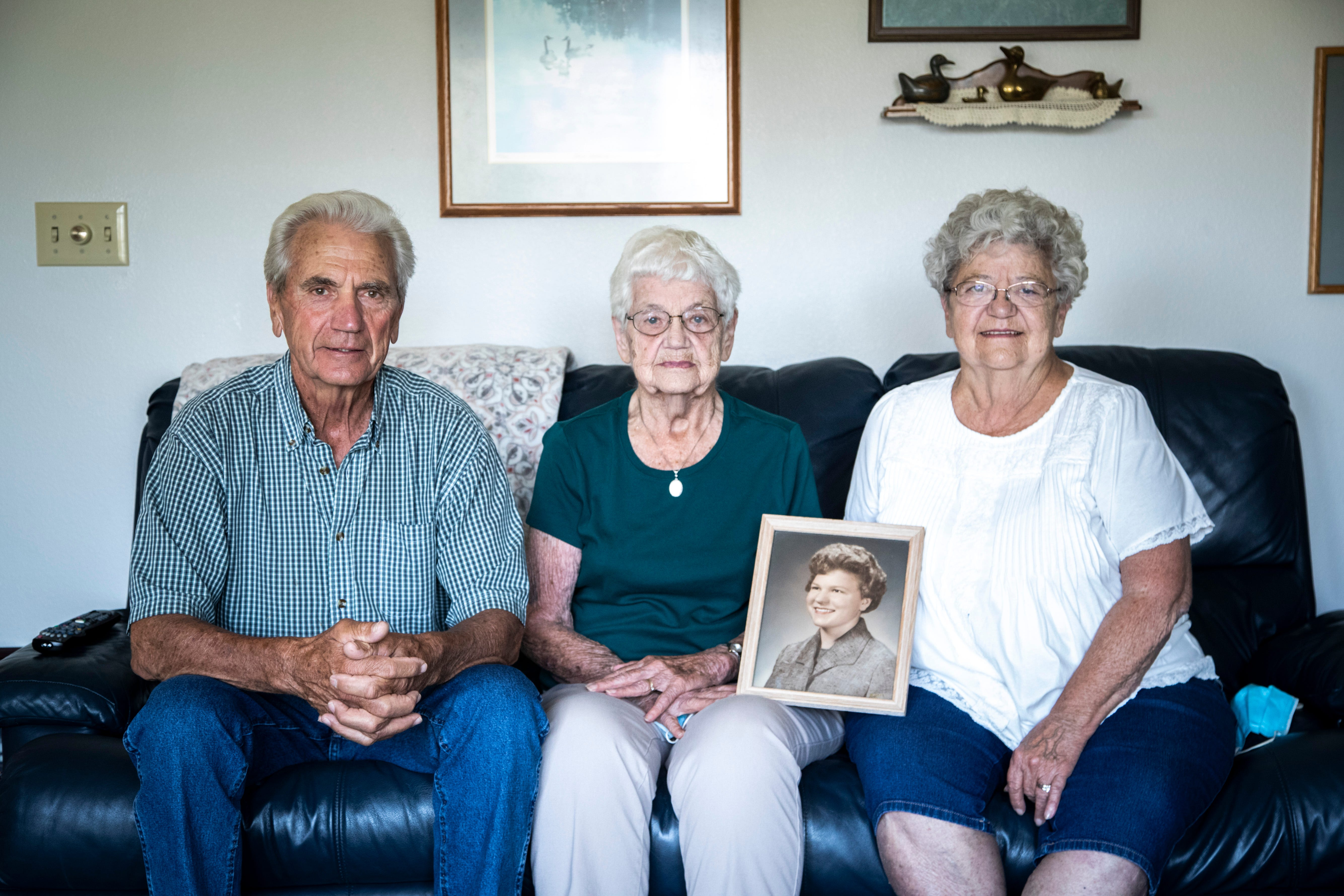 Siblings Jim Harney, Mary Ellen Glouhy and Virigina Ockenfels pose for a photo with a portrait of their sister, Theresa Harney.