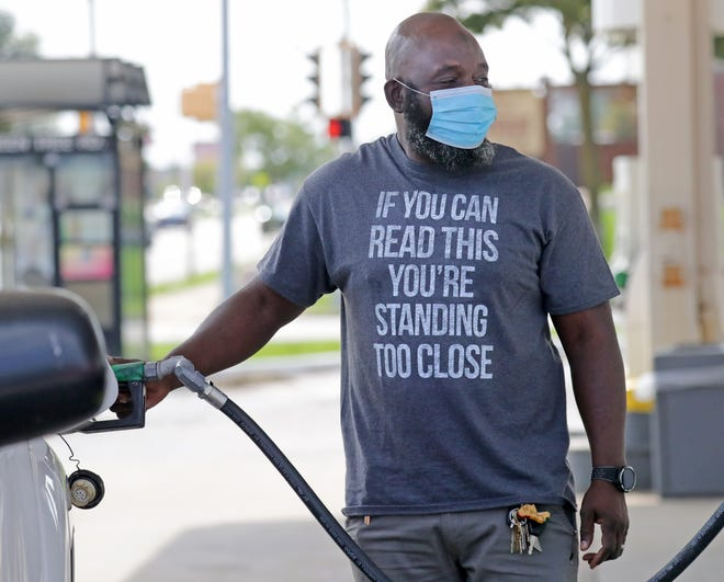 Abdul Djiguiba, of Milwaukee, wears a mask as he gets gas at a fueling station on the corner of Green Tree Road and North 76th Street in Milwaukee on Tuesday, Sept. 22, 2020. Gov. Tony Evers issued a new public health emergency on Tuesday to extend the statewide mask mandate until late November as cases of coronavirus accelerate around the state. - Mike De Sisti / Milwaukee Journal Sentinel