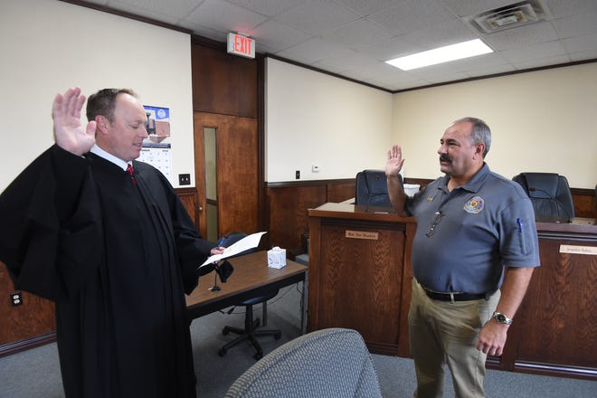 District Court Judge Jason Duffy, left, administers the oath of office to newly installed Mountain Home Fire Chief Kris Quick at city hall on Wednesday. Quick is long-serving veteran of the fire department and previously served as Assistant Chief.