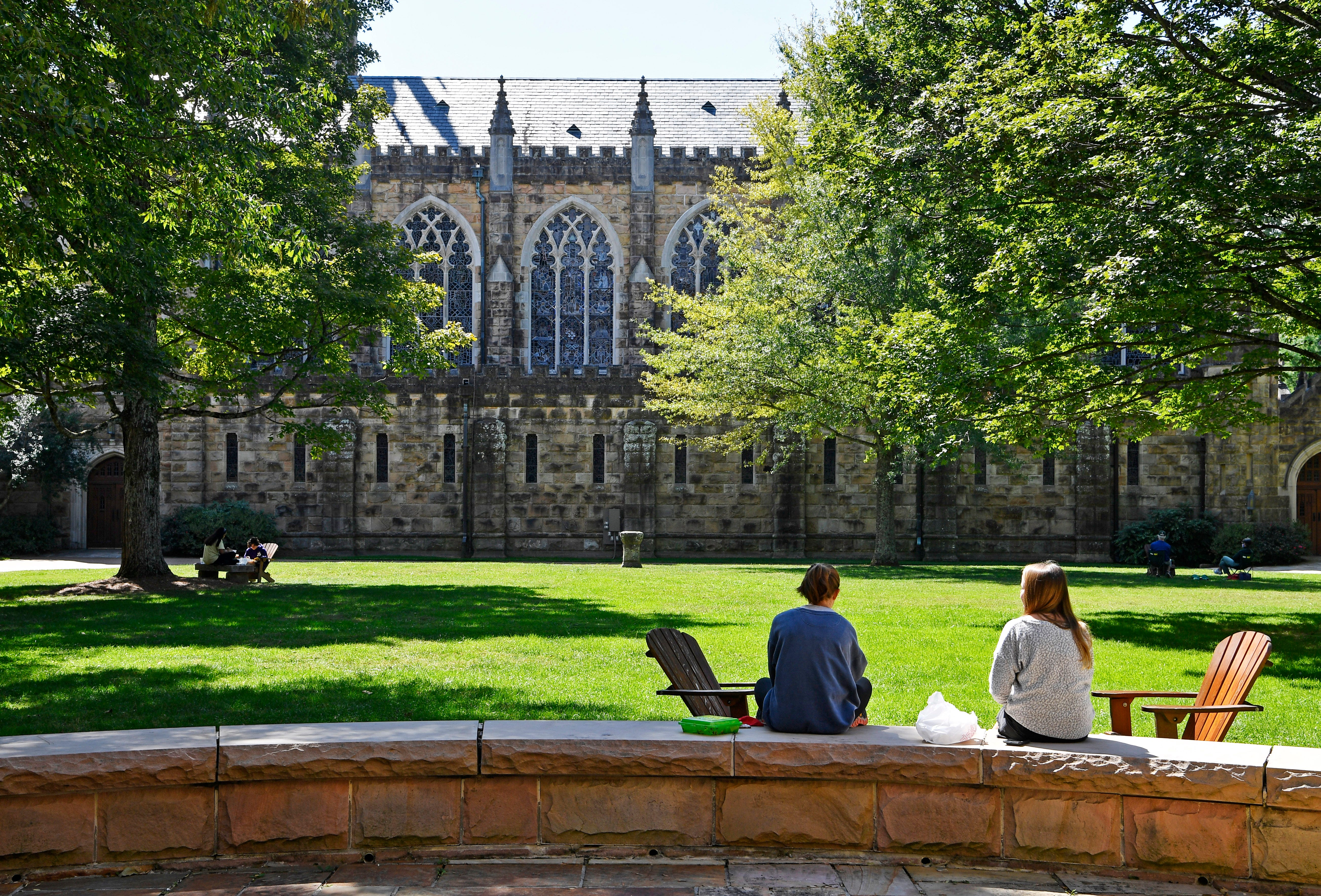 Two students sit and talk in an open area next to All Saints Chapel on the campus of the University of the South in Sewanee, Tenn. Tuesday, Sept. 22, 2020.