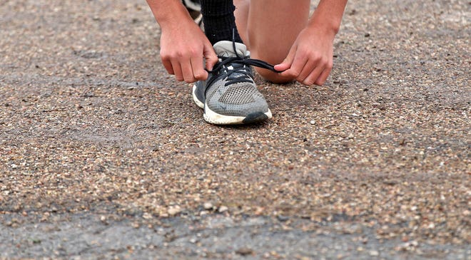 A runner ties his shoes prior to a race during a cross country meet in Miles on Wednesday, Sept. 23, 2020.