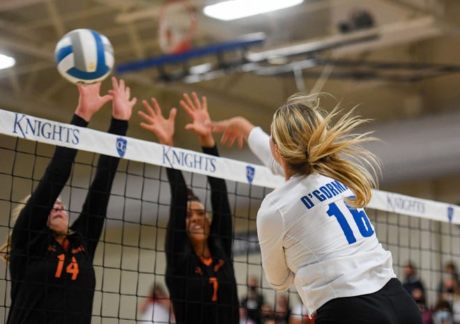 O'Gorman's Macy Matheson spikes the ball past Washington's Katy Richardson and Ndjakalenga Mwenentanda during their match on Tuesday, September 22, at O'Gorman High School in Sioux Falls.