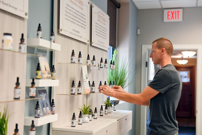 Matt Yde restocks shelves with tinctures on Wednesday, September 23, at Your CBD Store in Sioux Falls.