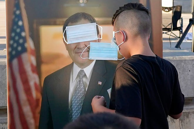 """FILE - In this Sept. 5, 2020 file photo, children play """"pin the mask on Gov. Gary Herbert"""" during a """"Trash Your Mask Protest"""" rally hosted by the Utah Business Revival at the Utah State Capitol in Salt Lake City. Herbert will increase pandemic restrictions in two Utah cities. But he stopped short of implementing any mask mandates state officials announced Tuesday, Sept. 22, 2020, as COVID-19 cases continue to surge in the state. (AP Photo/Rick Bowmer, File)"""