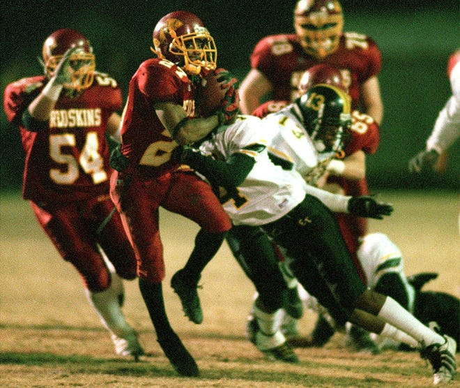 Tulare Union's Dominique Dorsey tries to break a tackle from Edison's Nate Brown during the first quarter at Bob Mathias Stadium Dec 1, 2000.