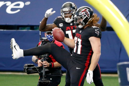 Atlanta Falcons' Julio Jones, left, and Hayden Hurst, right, celebrate a touchdown catch made by Hurst in the first half of an NFL football game against the Dallas Cowboys in Arlington, Texas, Sunday, Sept. 20, 2020.