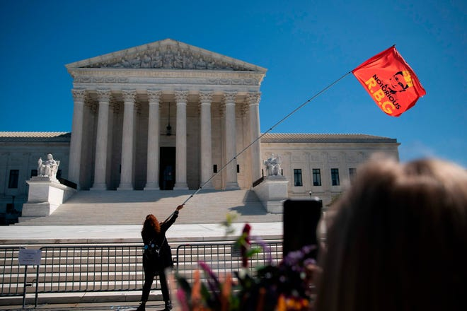 A woman waves an 'RBG' flag outside the US Supreme Court at a makeshift memorial for late US Supreme Court Justice Ruth Bader Ginsburg is seen near the steps of the Supreme Court on September 21, 2020, in Washington, D.C.