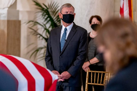 Chief Justice of the United States John Roberts and Associate Justice Elena Kagan, right, pay their respects as the flag-draped casket of Justice Ruth Bader Ginsburg arrives at the Supreme Court on Sept. 23.