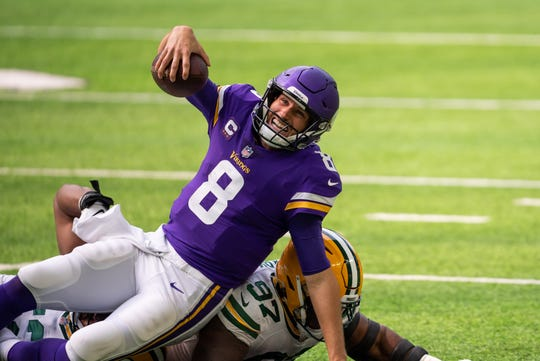 Minnesota Vikings quarterback Kirk Cousins (8) is tackled in the second quarter against the Green Bay Packers at U.S. Bank Stadium.