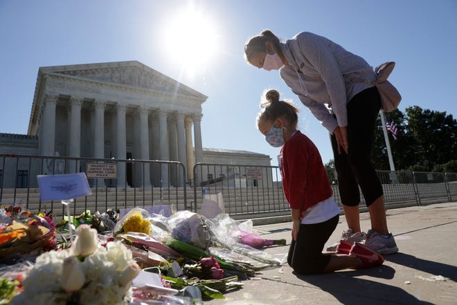 Five-year-old Abby Martin of Arlington, Virginia, pays respect with her mother Jackie Martin as they visit a makeshift memorial in front of the Supreme Court for the late Justice Ruth Bader Ginsburg on September 21, 2020, in Washington, D.C.