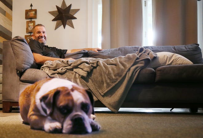 Steve MacAdam, the ODOT worker who was struck by a car, rests Thursday with Biggie, his English bulldog, who has been his companion as he recovers at his home in Stow.
