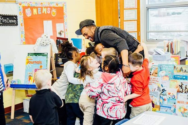 Akron Beacon Journal readers said they hope to start hugging their family, friends and neighbors again some time in 2021 after most receive the vaccination to protect against COVID-19. Ameer Williamson, a.k.a rapper/mentor Minus The Alien, gets a group hug from kids at Sieberling CLC after reading to them before the pandemic struck.