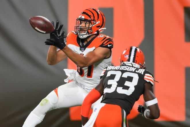 Cincinnati Bengals tight end C.J. Uzomah catches a touchdown pass next to Cleveland Browns' Ronnie Harrison Jr. during the first half of an NFL football game Thursday, Sept. 17, 2020, in Cleveland. (AP Photo/David Richard)