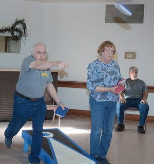 Dean Lair, left, tosses a bean bag during a 2019 corn toss game at the Alliance Area Senior Center.  Lair's teammate, at center, is his wife, Kay. At far right is scorekeeper Gary Lee.